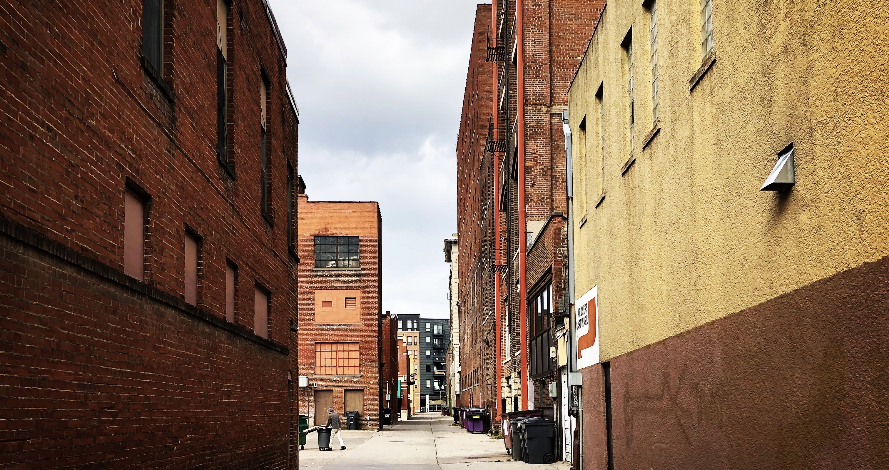 Photo of alley way with mid-size buildings on both sides in an urban setting.