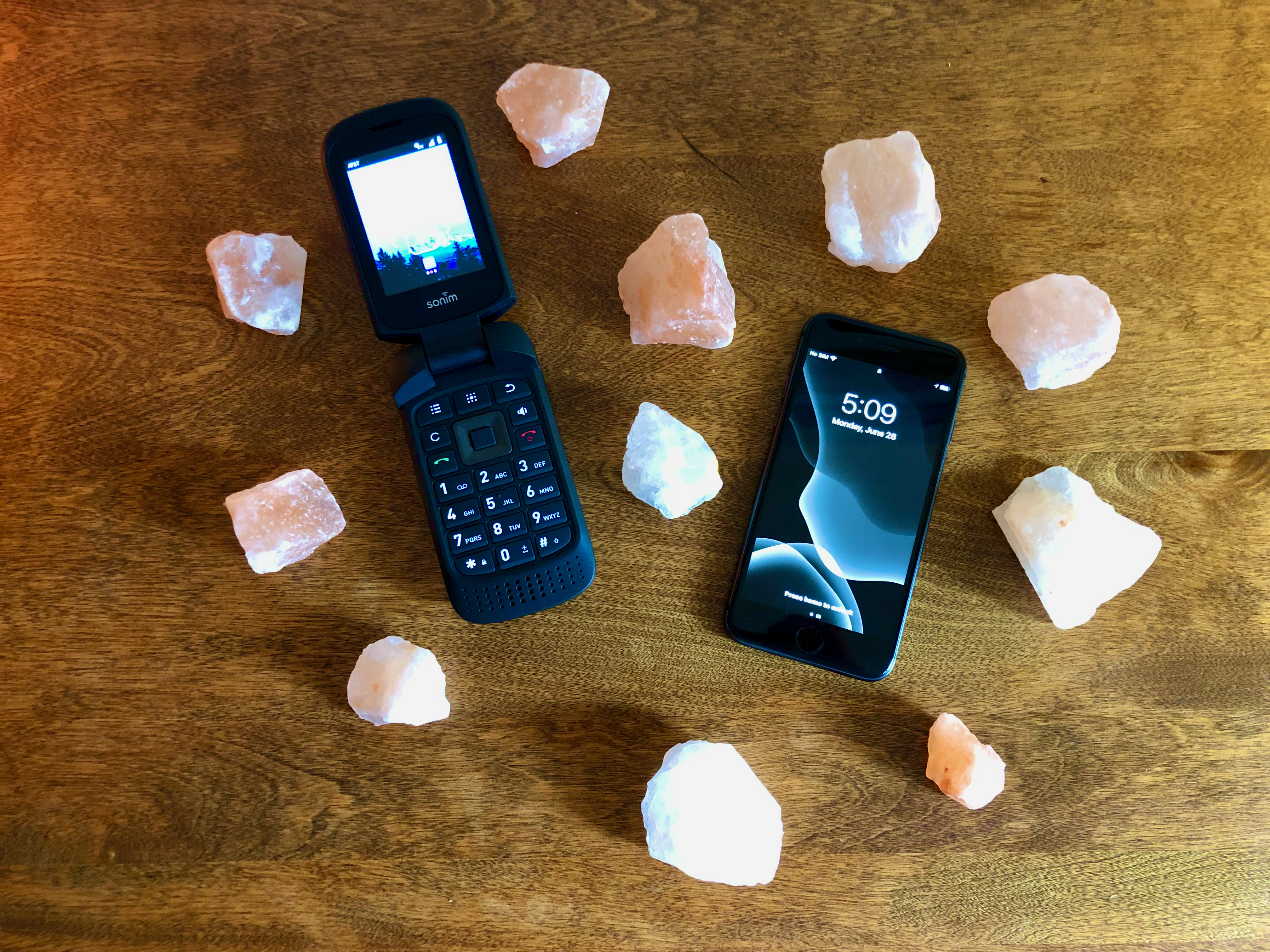 Image of a flip phone next to an iPhone, surrounded by small salt rocks.