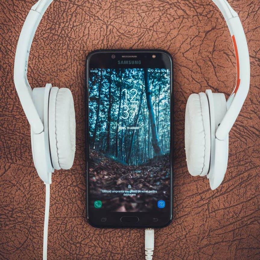 Picture of a smartphone in between a pair of headphones