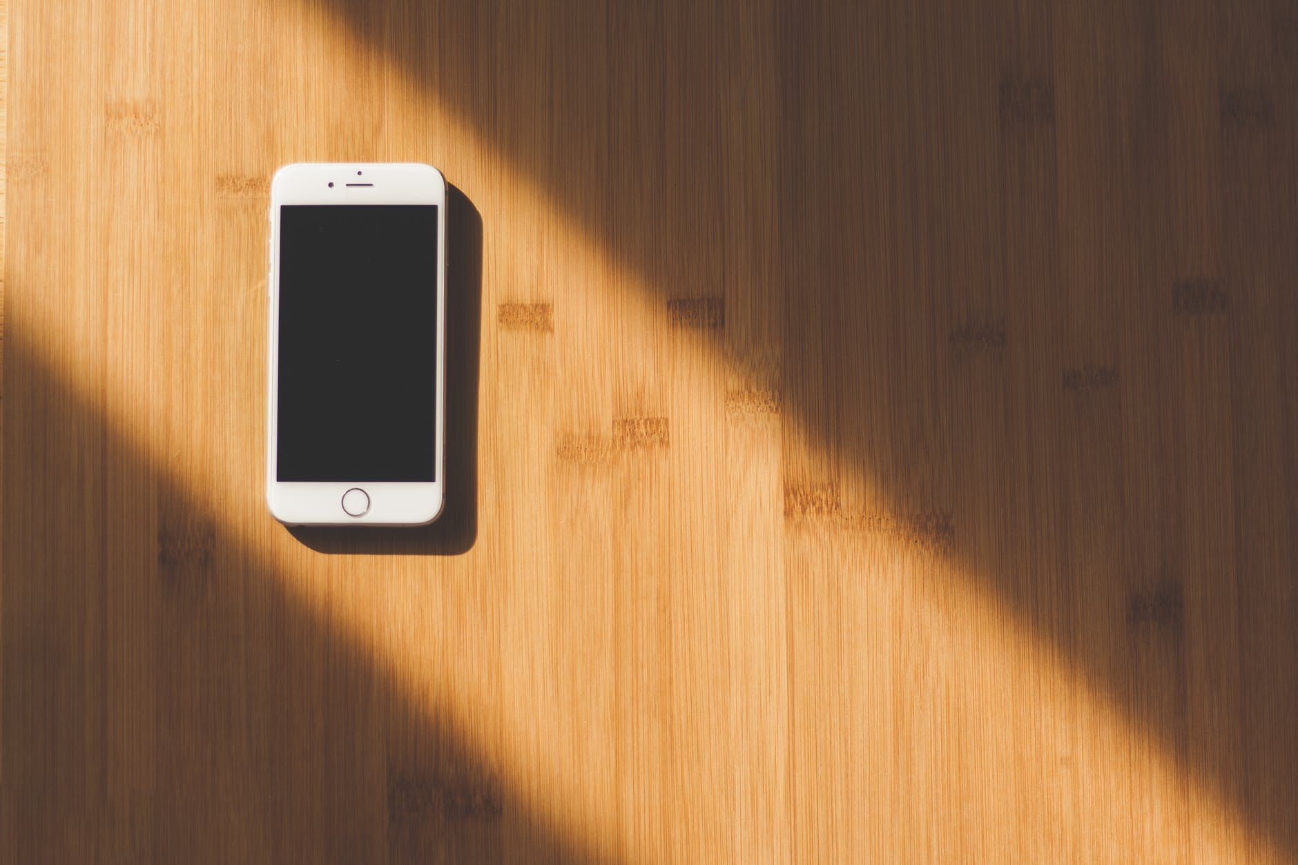 picture of a smart phone on a wooden desk with a ray of light illuminating the phone